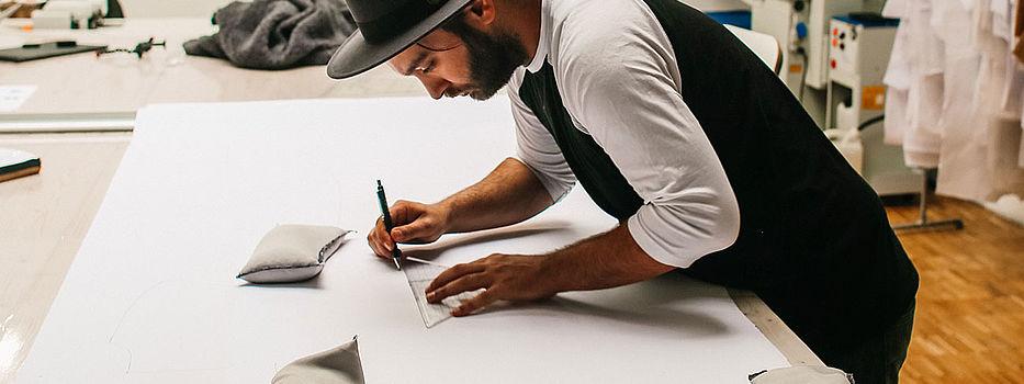 Oguzhan Deniz zeichnet etwas, vornübergebeugt an weißem Tisch.