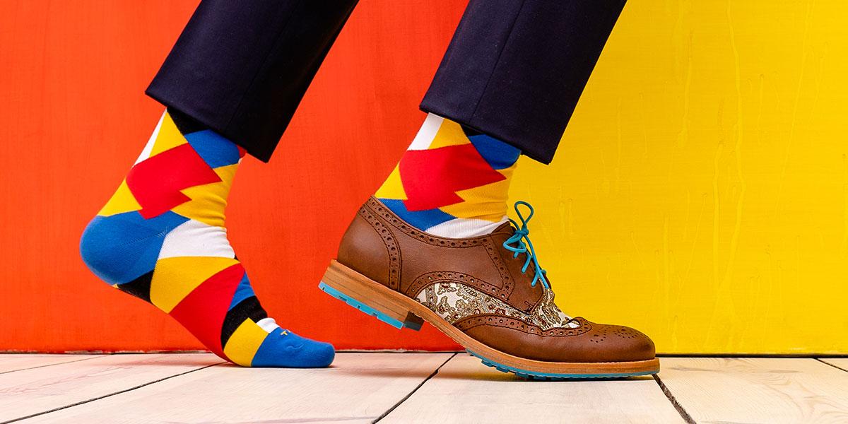Füße bis zur Wade mit bunten Socken und einem braunen Schuh mit englischem Muster: seitlich, vor rot gelber Wand