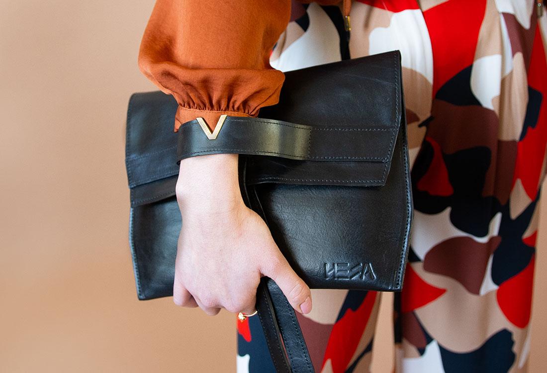 Hand, die schwarze Leder-Clutch von Hesa hält