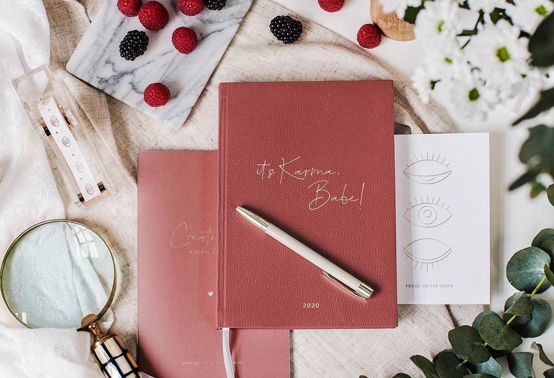 Rotes Notizbuch mit Stift und Lupe, Postkarte und Beeren drumherum