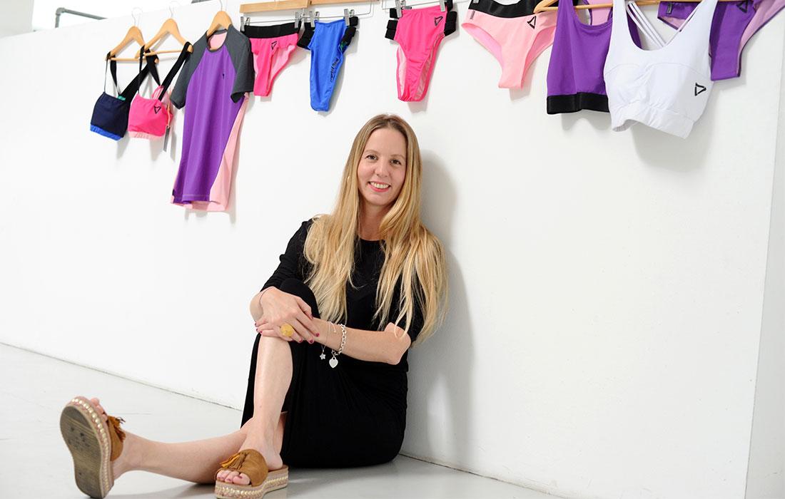 [Translate to Englisch:] Birgitta Tafelmeier sitzend vor einer Auswahl an Bade- und Sportmode
