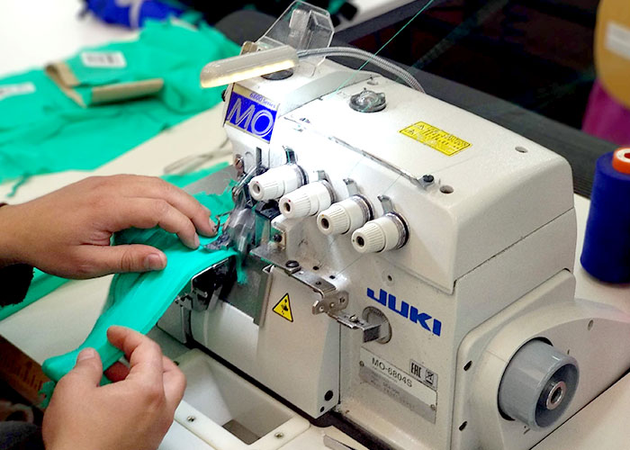 Green fabrics (Nylon Econyl) are sewed together with a sewing machine