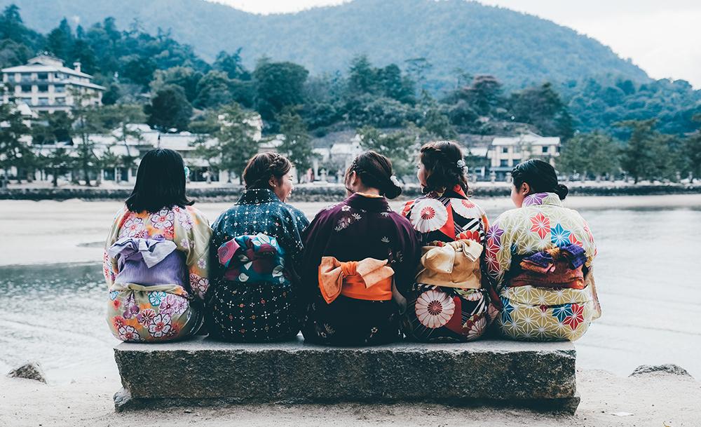 Mädchen sitzen auf einer Bank und tragen klassische Kimonos mit Obi