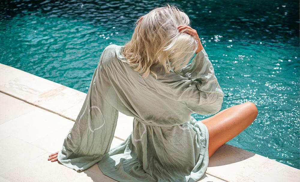 Frau, die einen Kimono am Pool trägt