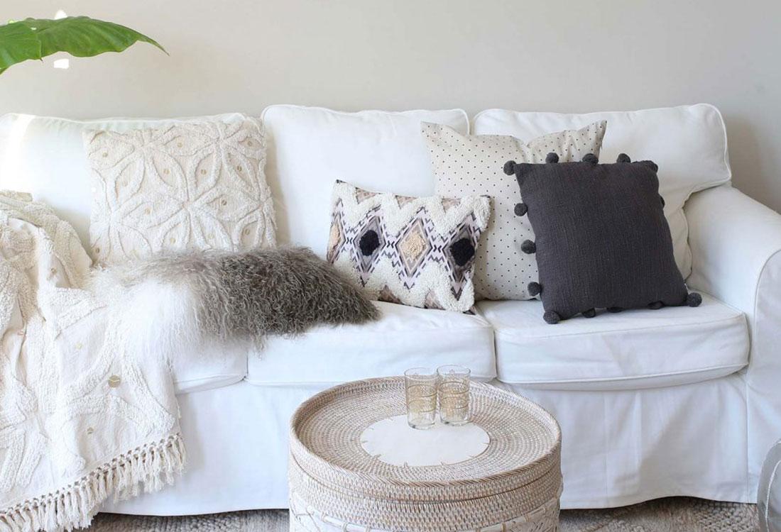 Weißes Sofa worauf verschiedenen Kissen liegen.