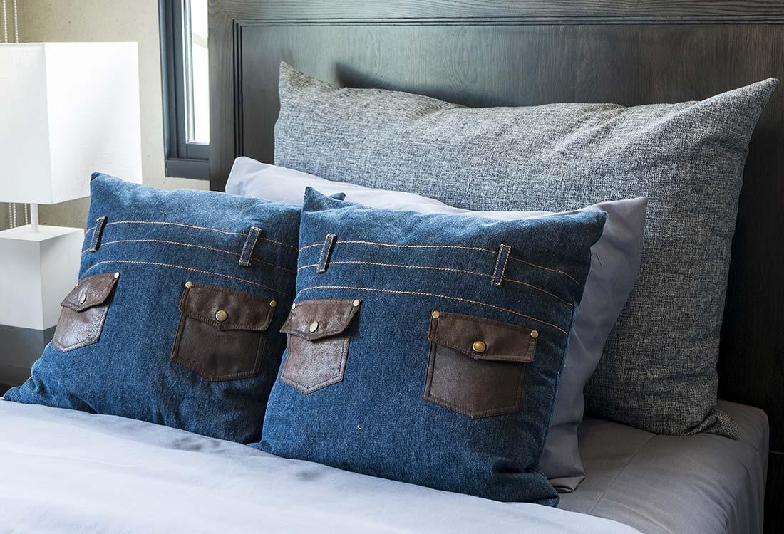 Zwei Kissen aus Jeans-Stoff auf einem Bett