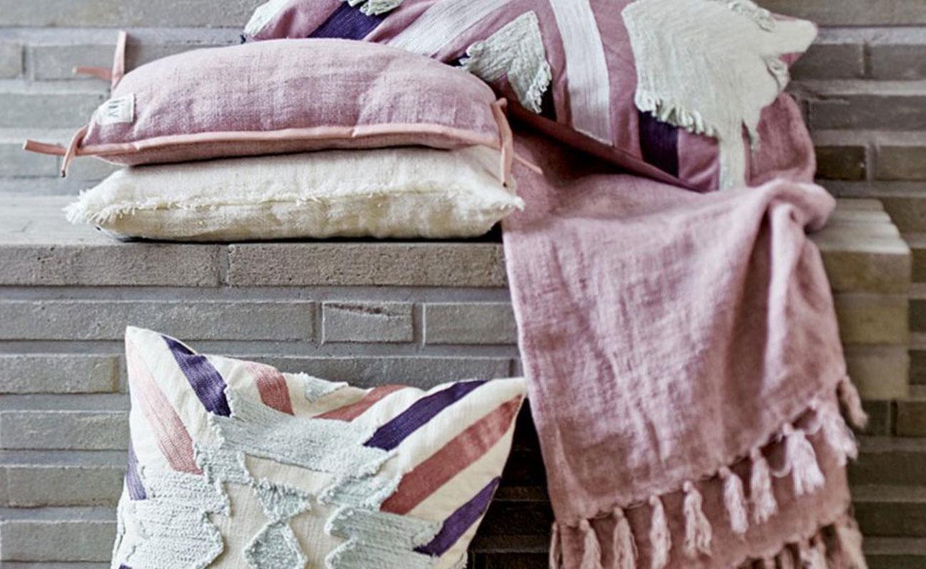 Mehrere aufeinander liegende pastellfarbene Kissen