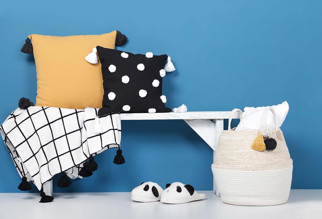 Zwei Kissen mit Pompoms auf einer Holzbank mit Pompoms. Davor stehen ein Korb und Panda-Hausschuhe.