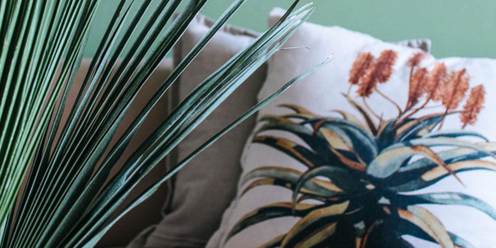Florales Kissen hinter einem Palmenblatt