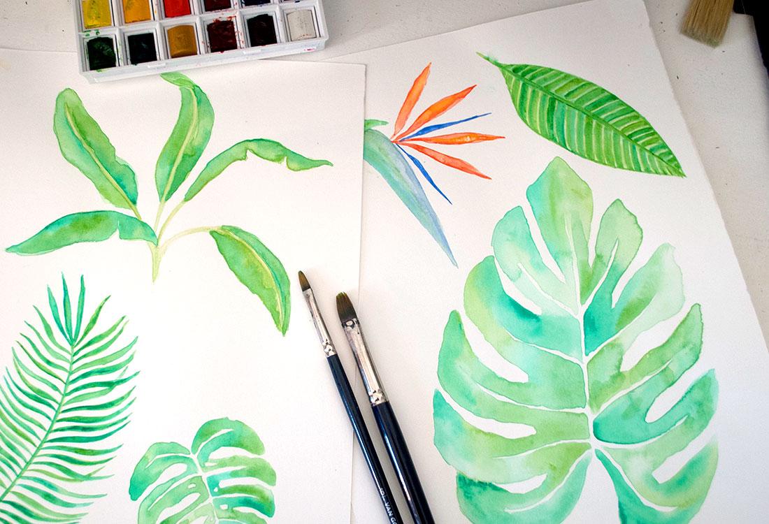 [Translate to Englisch:] Zwei Blätter auf denen mit Wasserfarben gemalte Blätter sind, zwei Pinsel und Wasserfarbenkasten