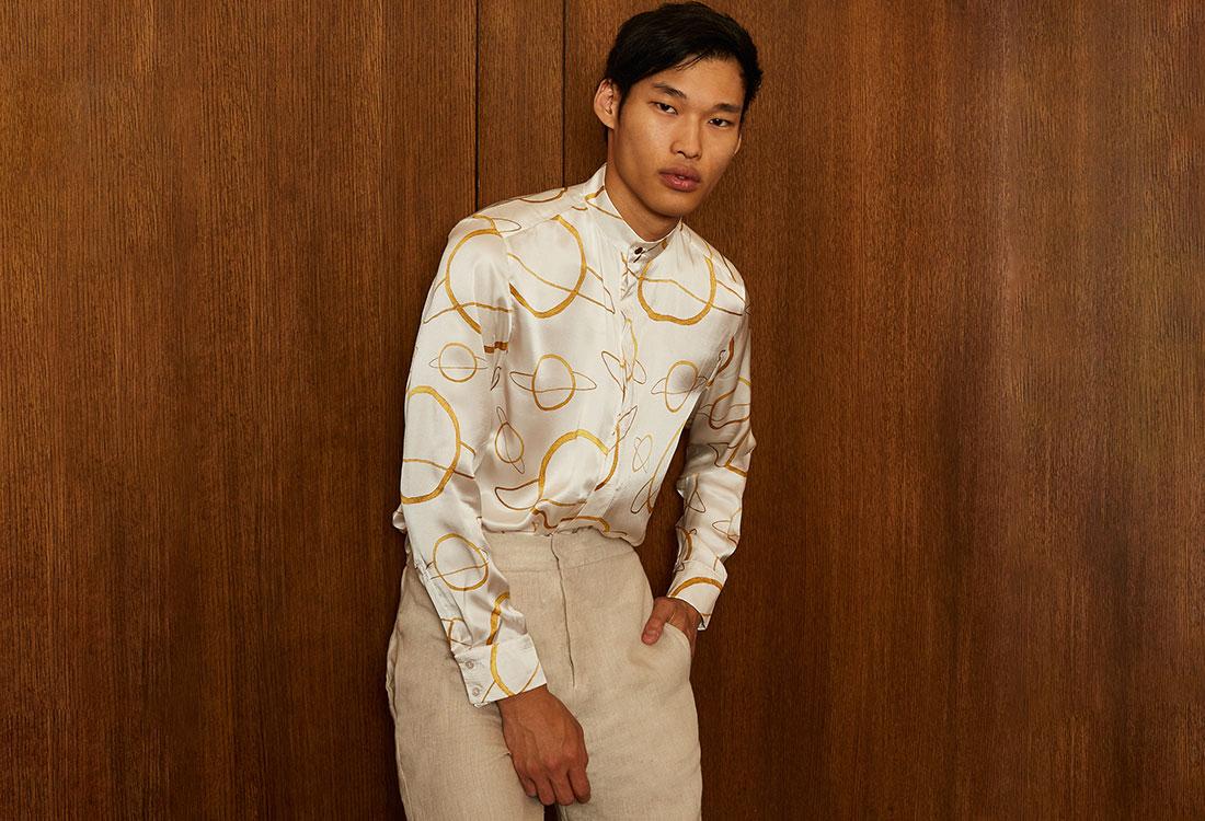 [Translate to Englisch:] Männliches Model mit Bluse mit Planetenmuster und beiger Hose
