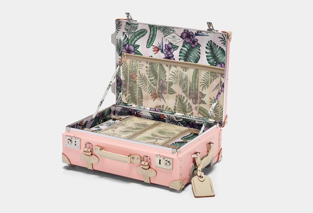 [Translate to Englisch:] Geöffneter rosaner Koffer mit Blätter- und Blütenprint innen