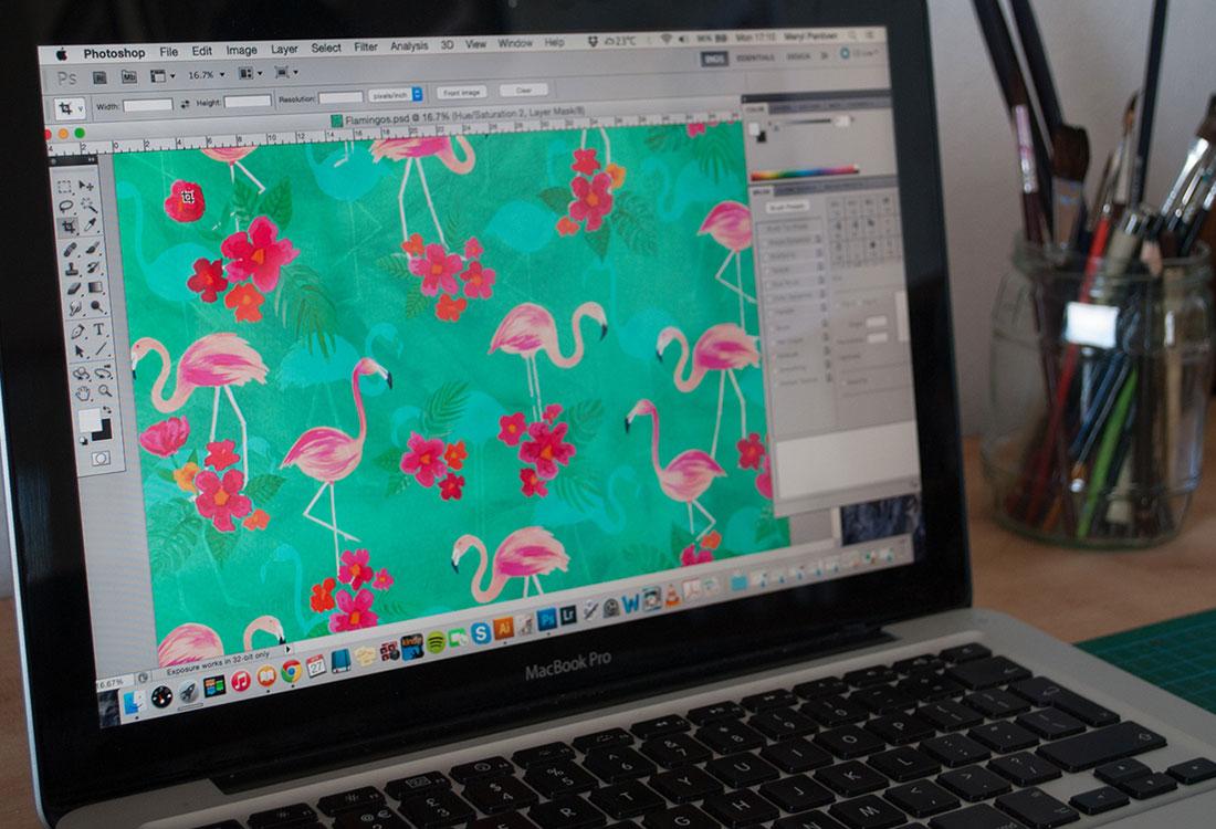 [Translate to Englisch:] Aufgeklappter Laptop mit geöffnetem Photoshop und Flamingos und Blütenmuster auf dem Bildschirm