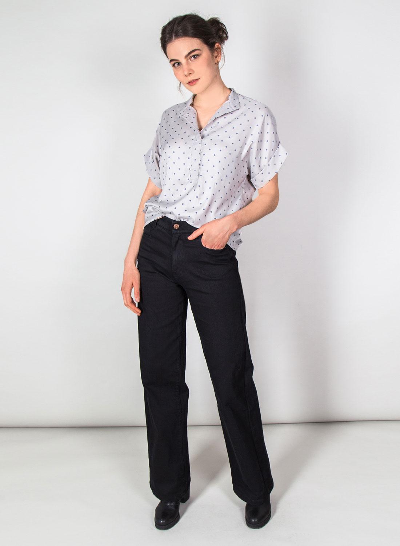 [Translate to Englisch:] Weibliches Model frontal mit kurzärmeliger heller Bluse mit Punkten und schwarzer Hose.