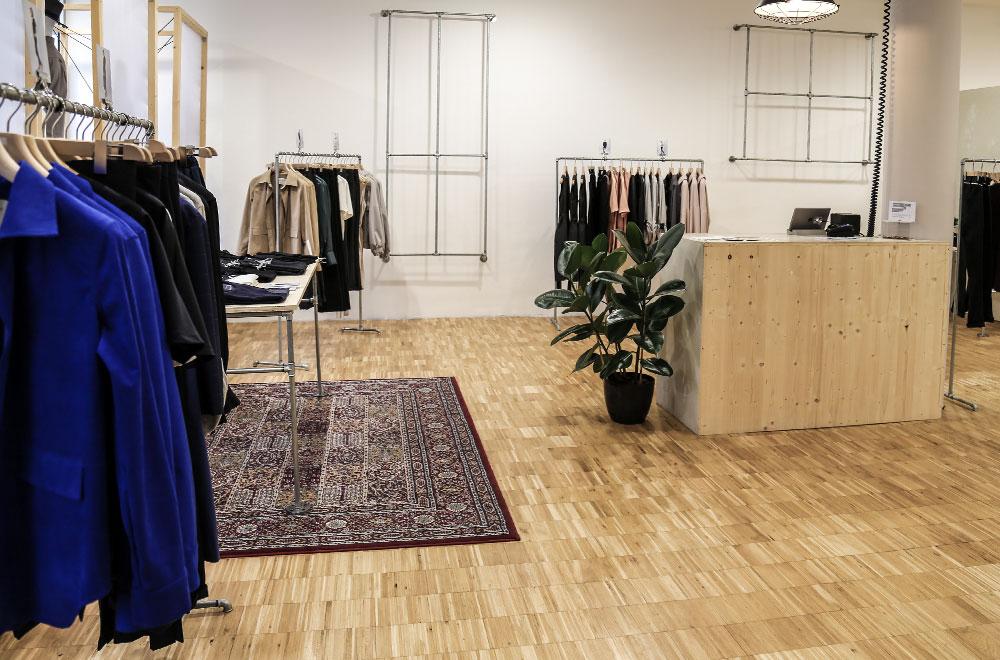 [Translate to Englisch:] Laden Wiederbelebt Kleiderstangen, Holboden und großem Teppich.