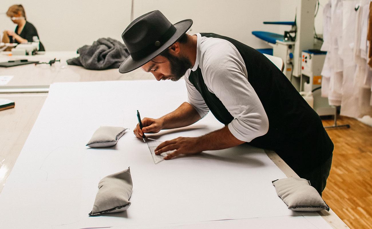 [Translate to Englisch:] Oguzhan Deniz zeichnet etwas, vornübergebeugt an weißem Tisch.