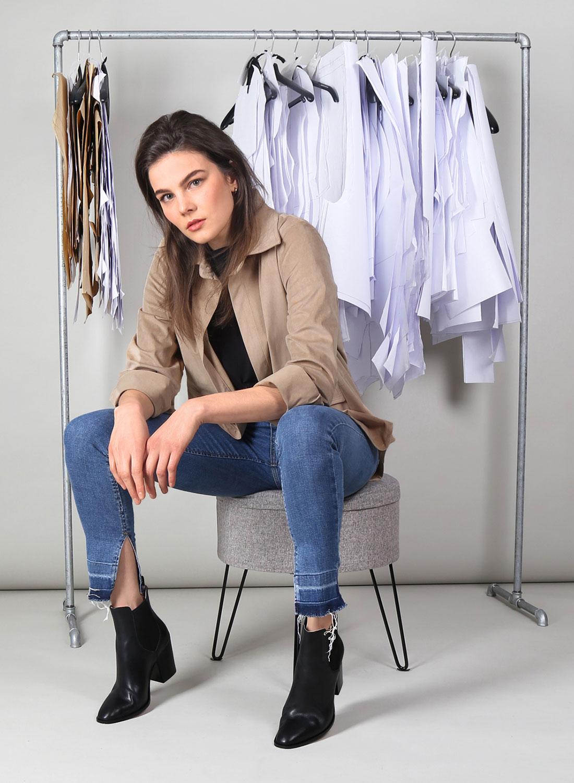[Translate to Englisch:] Weibliches Model, sitzend vor Kleiderstange mit hellbrauner Bluse, Bluejeans und schwarzen Stifeletten.