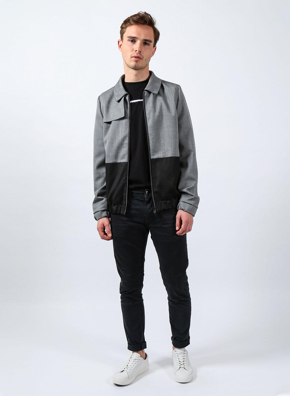 [Translate to Englisch:] Männliches Model mit grau-schwarzer Jacke, schwarzer Hose und weißen Sneakern.