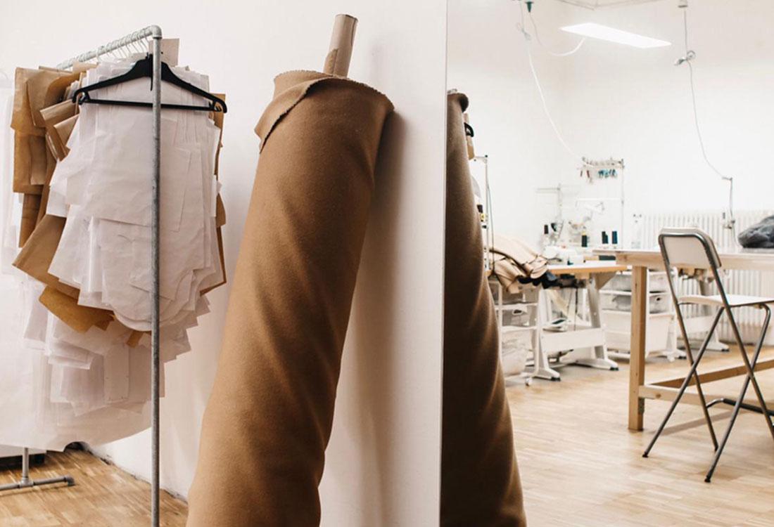 [Translate to Englisch:] Große braune Stoffrolle an die Wand gelehnt im Atelier, im Hintergrund Kleiderstange mit Schnittteilen.