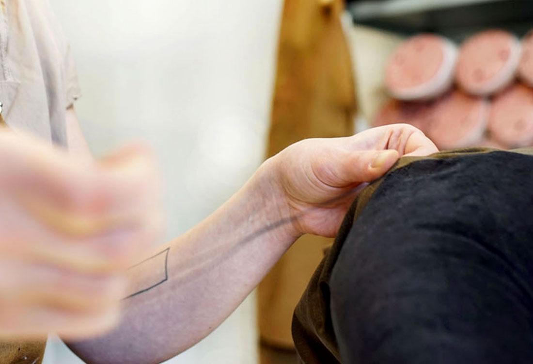 Inhaberin Silvia Wald beim Nähen eines flauschigen Kissens