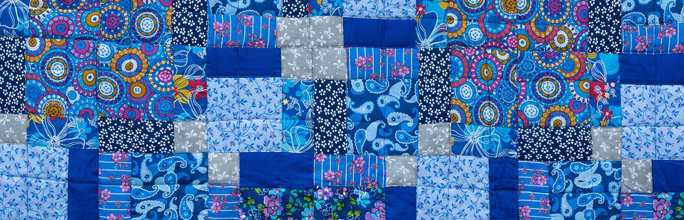 [Translate to Englisch:] Quilt in Blautönen mit verschiedenen Mustern