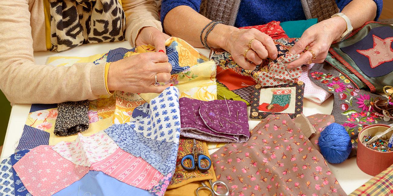 [Translate to Englisch:] Abbildung von zwei Frauen, welche Decken quilten