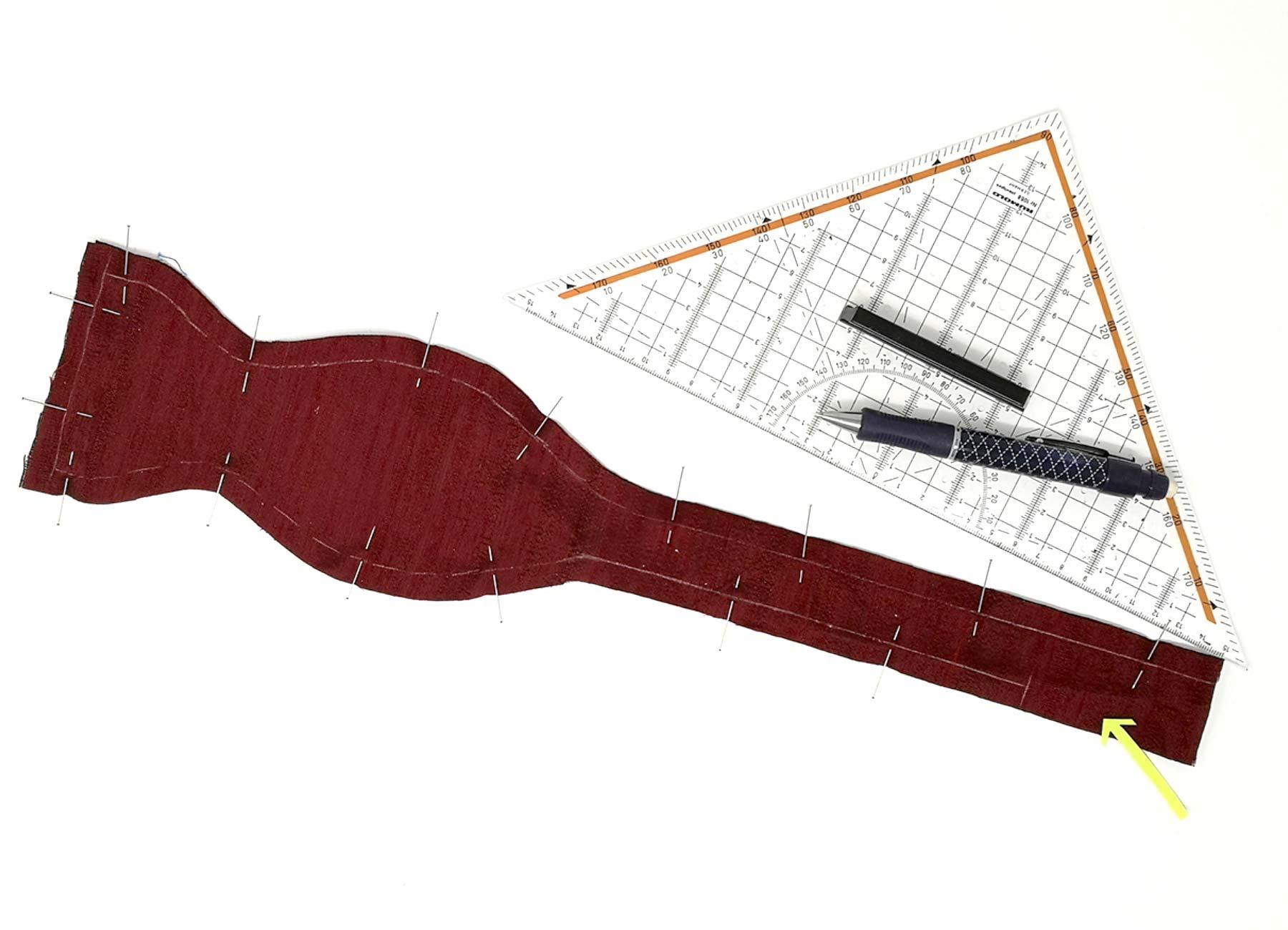 [Translate to Englisch:] Rotes Schnittteil für Fliege aus Wildseide, Geodreieck und Kugelschreiber